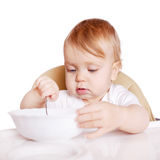 Baby eating by himself in high chair. Stock Image