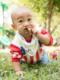 Baby eating a leaf. In public playground Royalty Free Stock Photos