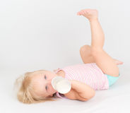 Baby eating milk from the bottle lie floor Royalty Free Stock Image