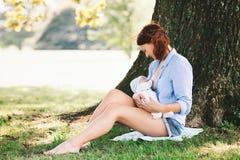 Mother breastfeeding newborn baby child on nature Royalty Free Stock Photo
