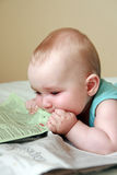 Baby eating newspaper Royalty Free Stock Image