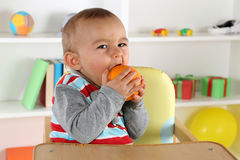 Baby eating orange fruit Royalty Free Stock Photography