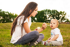 Baby eating outdoors. Young beautiful mother feeding her baby puree outdoors in sunlight Stock Image
