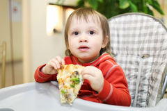 Baby eating pizza in cafe Stock Photography