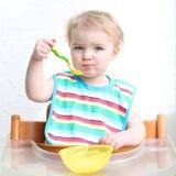 Baby eating porridge from bowl Stock Photography