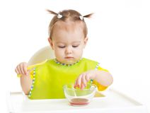 Baby eating and put fingers into food sitting at Stock Images