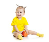 Baby eating red apple sitting on floor isolated stock photo
