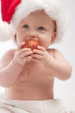 Baby eating red Xmas ball. Baby in Santa hat eating red Xmas ball Royalty Free Stock Photos
