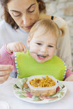 Baby eating rice from tupperware Royalty Free Stock Photography