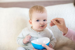 Baby eating while siting on the bed Royalty Free Stock Images