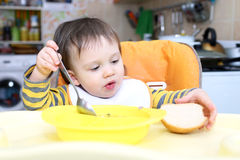 Baby eating soup and bread Royalty Free Stock Photos