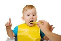 Baby eating spoon baby food jar.  Child feeding. Stock Photos