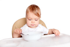 Baby eating with spoon in high chair Royalty Free Stock Photos