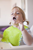 Baby eating spoon in mouth Royalty Free Stock Photos