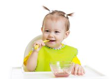Baby eating with spoon sitting at table Royalty Free Stock Photo