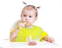 Baby eating with spoon sitting at table royalty free stock images