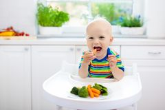 Baby Eating Vegetables In Kitchen. Healthy Food. Royalty Free Stock Photos
