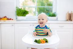Baby eating vegetables in kitchen. Healthy food. Royalty Free Stock Images