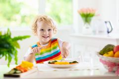 Baby eating vegetables. Solid food for infant. Child eating vegetables sitting in white high chair. Solid food for baby. Little boy eating healthy vegetable stock photography