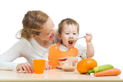 Baby eating vegetables by spoon himself and mother stock photography
