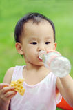 Baby eating waffle and drink water Stock Image