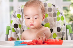 Baby eating watermelon with hands Stock Image