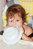 Baby eating yogurt and soiled face. Baby with curly hair and blue eyes eating cottage cheese or yogurt and soiled face, hands, and all around the table. He Stock Photos