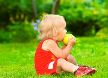 Baby eats an apple Stock Image