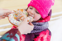 Baby eats bagel in park Stock Images