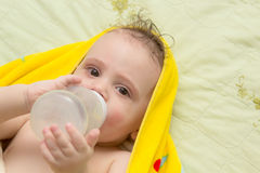 Baby eats from a bottle. The baby while lying eats from a bottle Stock Images