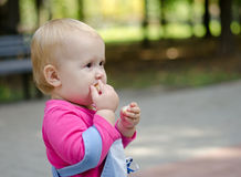 Baby eats a bun. Child standing in a park and eating a bun stock photos