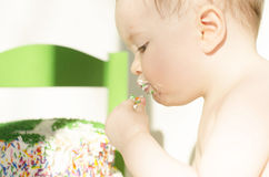 A baby eats cake royalty free stock image