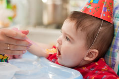 Baby eats porridge. The child eats porridge on the birthday royalty free stock photography