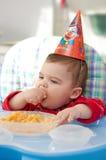 Baby eats porridge. The child eats porridge on the birthday stock photography