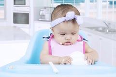 Baby eats porridge in kitchen Royalty Free Stock Photography