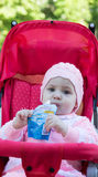 The baby eats a puree from a supermarket Stock Photography