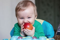 Baby eats red apple Royalty Free Stock Photos