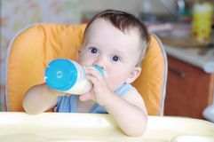 Baby eats from small bottle Stock Photo