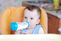 Baby eats from small bottle. Baby age of 10 months eats from small bottle Stock Photo