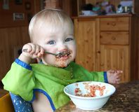 Baby eats with a spoon quinoa with vegetables Stock Image