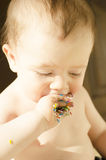 A baby eats sprinkles Royalty Free Stock Images
