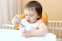 Baby eats youghourt Royalty Free Stock Images