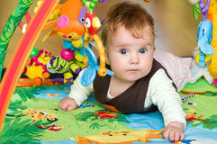 Baby in educational mat. Cute baby girl lying in colorful educational mat royalty free stock images