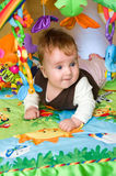 Baby in educational mat. Cute baby girl lying in colorful educational mat royalty free stock photo