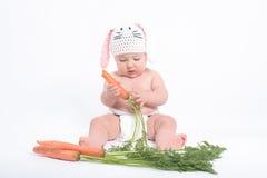 Baby in een kostuum van konijn het knagen aan wortel Stock Fotografie