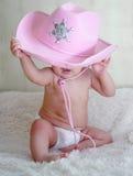 Baby in een roze zitting van de cowboyhoed in luiers op de laag Stock Foto's
