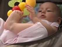 Baby in een wandelwagen met een rammelaar stock afbeeldingen
