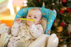 Baby in einem Fütterungssitz Stockbild