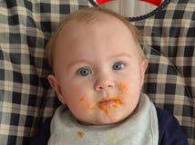 Baby in einem Hochstuhl zur Abendessenzeit Stockfotografie