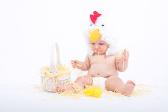 Baby in einem Kostüm des Hahns sitzend in einem zerstreuten Heu Stroh kauend, stockbild